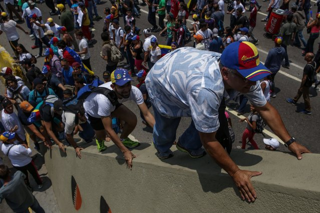 Hundred of people protest while some climb a bridge in Caracas, Venezuela, on 10 April 2017. The security forces of Venezuela disperse, for fifth time in the last days, an opposition protest with the participation of hundred of people that demonstrate against the Supreme. (Photo by Cristian Hernández/EPA)