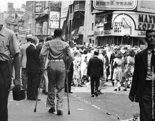 A rear veiw of a soldier on crutches in a crowd in Times Square on VJ Day, New York City, August 1945