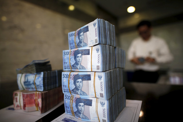 A teller in Bank Indonesia's headquarters counts rupiah bank notes in Jakarta, Indonesia April 21, 2016. (Photo by Darren Whiteside/Reuters)