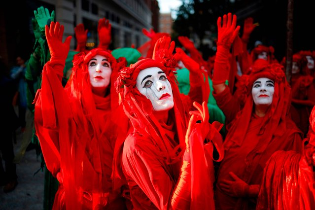 "Protesters in costume gather at Marble Arch in London at an opening ceremony to mark the beginning of the International Rebellion on October 6, 2019, an event organised by Extinction Rebellion. Extinction Rebellion climate protesters are planning to bring disruption to 60 cities around the world from Monday in a fortnight of civil disobedience, warning of an environmental ""apocalypse"". (Photo by Tolga Akmen/AFP Photo)"
