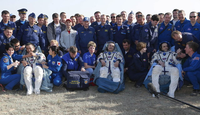 From left, Japanese astronaut Koichi Wakata, Russian cosmonaut Mikhail Tyurin and U.S. astronaut Rick Mastracchio sit in chairs shortly after the landing of the Russian Soyuz TMA-11 space capsule about 150 kilometers (93 miles) southeast of the Kazakh town of Dzhezkazgan, Kazakhstan, Wednesday, May 14, 2014. The Soyuz space capsule with Wakata, Tyurin and Mastracchio returning from a half-year mission to the International Space Station landed safely Wednesday on the steppes of Kazakhstan. (Photo by Dmitry Lovetsky/AP Photo)