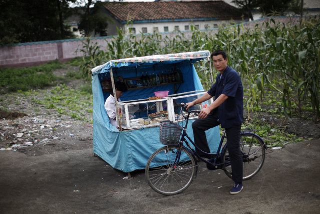 A man on his bicycle is seen next to a local vendor near the North Korean Special Economic Zone of Rason City in Rajin, northeast of Pyongyang August 29, 2011. (Photo by Carlos Barria/Reuters)