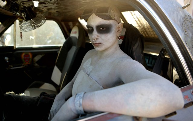 A woman poses for pictures in her car during Wasteland Weekend festival at the Mojave desert in Edwards, California on September 28, 2019. In 2019 the world's largest post-apocalyptic festival celebrates its 10th anniversary with around 4,000 attendees. The organizers require all festival goers to be in costume, with the idea of creating a full-inmersion effect, making attendees feel like they're inside a Mad Max-style movie for 5 days. Activities include any number of themed distractions from the real world: live bands, DJs, car cruises, costume contests, a film festival, a post-apocalyptic swimsuit competition, Thunderdome battles etc. (Photo by Agustin Paullier/AFP Photo)