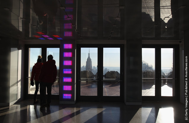 Tourists walk onto an observation deck atop Rockefeller Center as the Empire State Building towers over the Manhattan skyline
