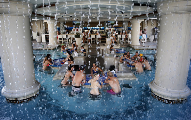 In this Tuesday, July 7, 2015 photo, people play blackjack in a pool at Caesars Palace in Las Vegas. (Photo by John Locher/AP Photo)