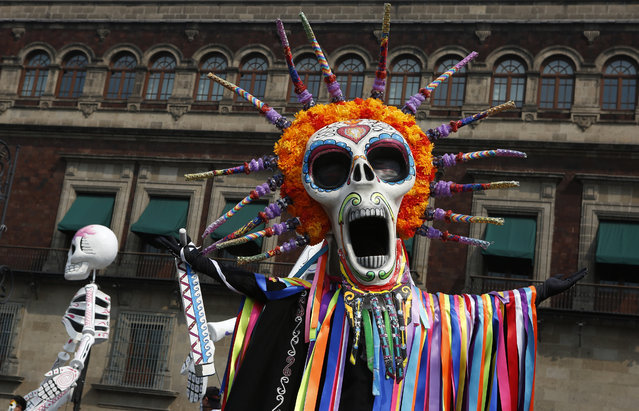 "Performers in costume attend a Day of the Dead parade in Mexico City, Sunday, October 27, 2019. The parade on Sunday marks the fourth consecutive year that the city has borrowed props from the opening scene of the James Bond film, ""Spectre,"" in which Daniel Craig's title character dons a skull mask as he makes his way through a crowd of revelers. (Photo by Ginnette Riquelme/AP Photo)"