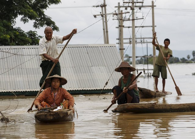 People row their canoes on a flooded street at a village in Kawlin township, Sagaing division, Myanmar, July 21, 2015. (Photo by Soe Zeya Tun/Reuters)