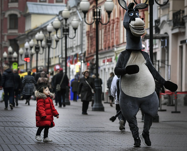 A young girl looks at an animator in downtown Moscow, Russia on November 5, 2019. (Photo by Alexander Nemenov/AFP Photo)