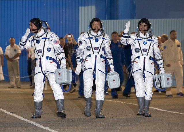 The International Space Station (ISS) crew members (L to R) Kjell Lindgren of the U.S., Oleg Kononenko of Russia and Kimiya Yui of Japan walk after donning space suits at the Baikonur cosmodrome, Kazakhstan, July 23, 2015. (Photo by Shamil Zhumatov/Reuters)