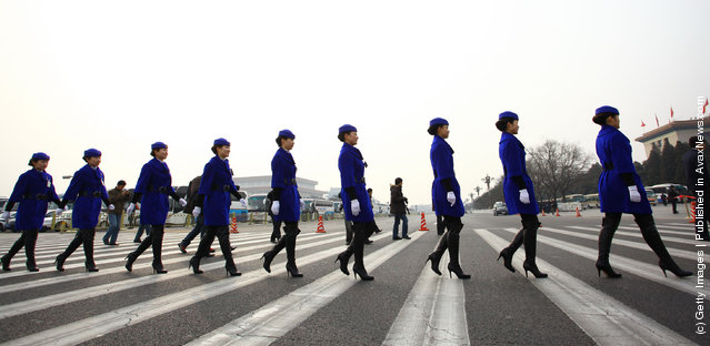 Hostesses for the National People's Congress (NPC)  walk across in front of the Great Hall of the People on March 5, 2012 in Beijing, China