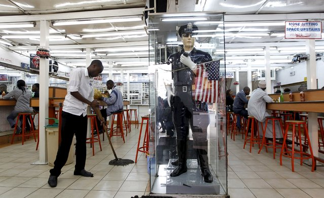 A worker cleans the floor near a statue depicting an officer from the New York Police Department (NYPD) at the entrance of a fast-food restaurant, ahead of a scheduled state visit by U.S. President Barack Obama, in Kenya's capital Nairobi July 23, 2015. Obama will land in Kenya on Friday with a mission to strengthen U.S. security and economic ties, but his personal connection to his father's birthplace will dominate a trip that Kenyans view as a native son returning home. (Photo by Thomas Mukoya/Reuters)