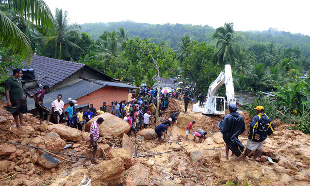 Sri Lankans watch military rescue efforts at the site of a landslide at Bellana village in Kalutara district, Sri Lanka, Friday, May 26, 2017. Mudslides and floods triggered by heavy rains in Sri Lanka killed dozens and left many more missing on Friday. (Photo by Eranga Jayawardena/AP Photo)