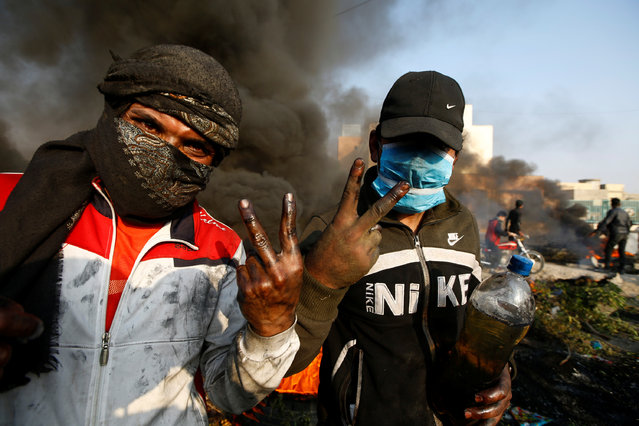 Iraqi demonstrators pose for a photo as they burn tires to block a street during ongoing anti-government protests in Najaf, Iraq on November 27, 2019. (Photo by Alaa al-Marjani/Reuters)