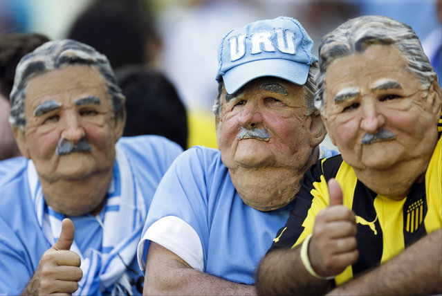 Masked fans from Uruguay wait for the start of the group D World Cup soccer match between Uruguay and Costa Rica at the Arena Castelao in Fortaleza, Brazil, Saturday, June 14, 2014. (Photo by Natacha Pisarenko/AP Photo)
