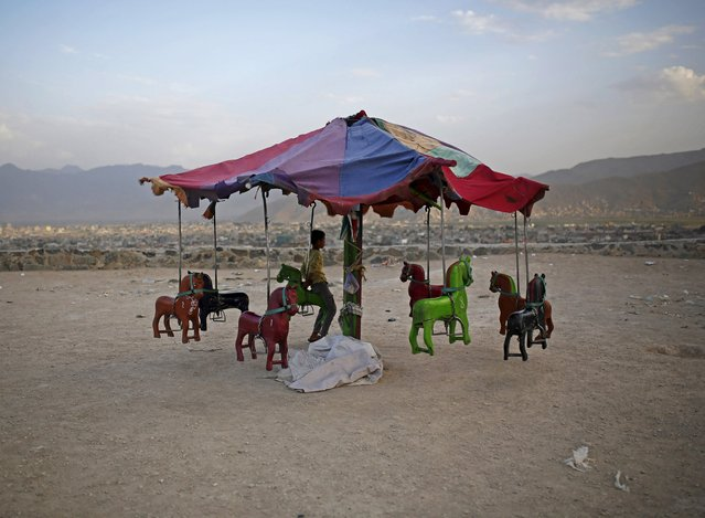 An Afghan boy sits on a merry-go-round on a hill top in Kabul July 20, 2015. (Photo by Ahmad Masood/Reuters)