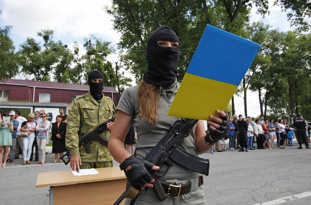"""A member of the """"Donbass"""" self-defence battalion swears the oath to be officially included into the reserve battalion of the National Guard of Ukraine near Kiev June 23, 2014. (Photo by Valentyn Ogirenko/Reuters)"""