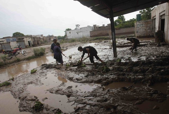 Workers remove mud from the front of their shops after heavy rainfall caused flooding in Peshawar, Pakistan, July 27, 2015. (Photo by Fayaz Aziz/Reuters)