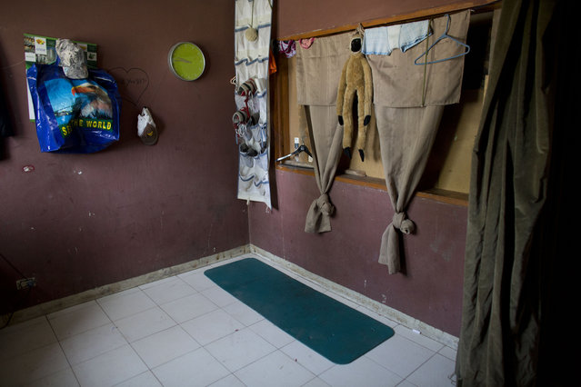 In this June 26, 2015 photo, a worn yoga mat is the only padding to sleep on for a family of three living in one room of an abandoned shipping depot in Port-au-Prince, Haiti. The six squatter families residing in the building have each taken an office as a bedroom, but at night, they say, other homeless workers come to sleep on the floor in the depot and hallways. (Photo by Rebecca Blackwell/AP Photo)