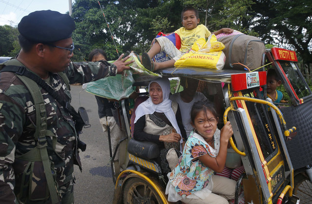 Residents fleeing the besieged city of Marawi are questioned at a checkpoint by government soldiers, Friday, May 26, 2017, in Bal-oi township, southern Philippines. (Photo by Bullit Marquez/AP Photo)
