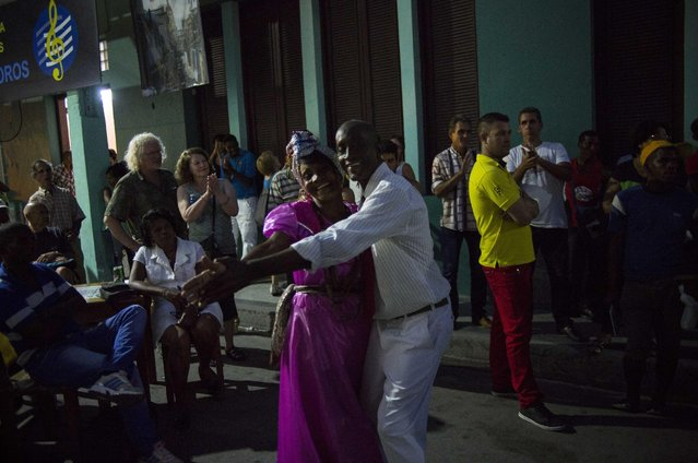 In this March 21, 2015 photo, seniors dance in the street for tourists at night in Santiago, Cuba. Life in Cuba in 2015 is a race between hope and desperation, as a staggering economy pushes some towards new ways of living and others toward hopelessness, anger and emigration. (Photo by Ramon Espinosa/AP Photo)