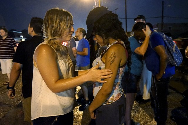 Two white women lead two black  women in prayer at the site of last year's riots on the one year anniversary of the killing of Michael Brown in Ferguson, Missouri August 9, 2015. (Photo by Rick Wilking/Reuters)