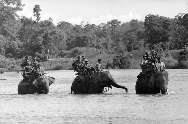 South Vietnamese soldiers ride elephants across a river in the Ba Don area, about 20 miles from the Cambodian border, during a patrol in search of Viet Cong guerrillas in June 1964
