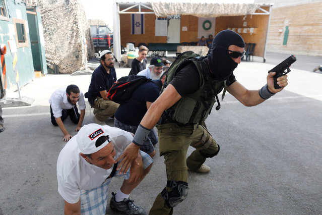 "A group of tourists take part in a two hour ""boot camp"" experience, at ""Caliber 3 Israeli Counter Terror and Security Academy"" in the Gush Etzion settlement bloc south of Jerusalem in the occupied West Bank on July 13, 2017. It is part of a counter-terrorism ""boot camp"" organised by Caliber 3, a company set up by a colonel in the Israeli army reserves. (Photo by Nir Elias/Reuters)"