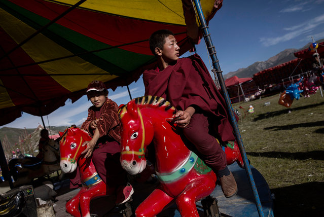 Tibetan Buddhist monks sit on a carousel at a local festival on July 26, 2015 on the Tibetan Plateau in Yushu County, Qinghai, China. (Photo by Kevin Frayer/Getty Images)