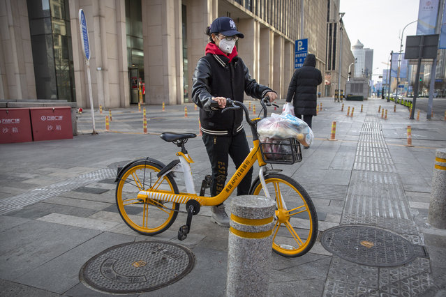 """A woman wears a face mask as she pushes a bicycle along a street in Beijing, Saturday, February 1, 2020. China's death toll from a new virus rose to 259 on Saturday and a World Health Organization official said other governments need to prepare for """"domestic outbreak control"""" if the disease spreads in their countries. (Photo by Mark Schiefelbein/AP Photo)"""