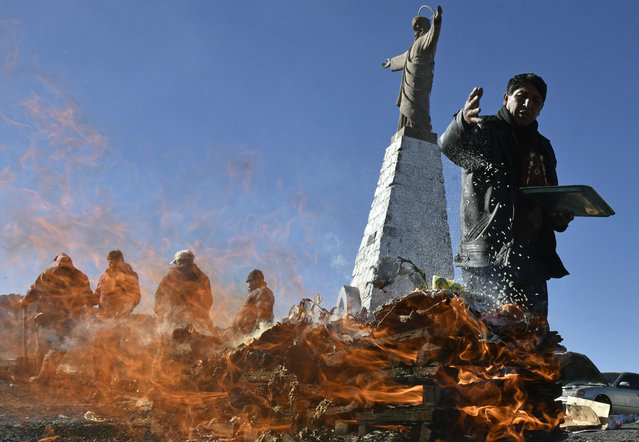 A Yatiri (Aymara priest) performs an Andean ritual burning sullus (llama fetus) to thank the Pachamama (Mother Earth), 25 Kilometres North of La Paz on August 1, 2017 Bolivia worships during August the Andean goddess, Pachamama. (Photo by Aizar Raldes/AFP Photo)