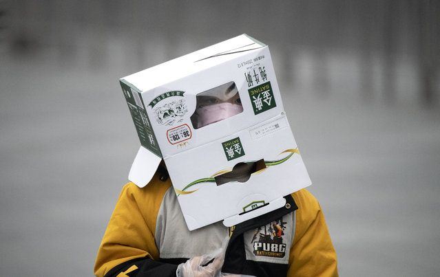 A boy wears a cardboard box on his head at the Shanghai Railway station in Shanghai on February 13, 2020. The number of deaths and new cases from China's COVID-19 coronavirus outbreak spiked dramatically on February 13 after authorities changed the way they count infections in a move that will likely fuel speculation that the severity of the outbreak has been under-reported. (Photo by Noel Celis/AFP Photo)