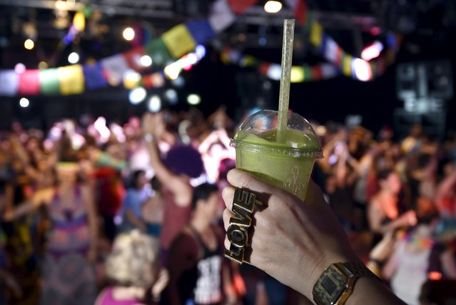 """A reveller holds her cup of fruit smoothie at """"Morning Gloryville"""" at the Ministry of Sound in south London August 11, 2015. (Photo by Toby Melville/Reuters)"""