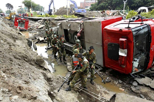 Soldiers use electronic sensors to search for missing firefighters under a line of fire trucks caught in massive gas explosions in Kaohsiung, Taiwan, Friday, August 1, 2014. A series of underground explosions about midnight Thursday and early Friday ripped through Taiwan's second-largest city, killing scores of people, Taiwan's National Fire Agency said Friday. (Photo by Wally Santana/AP Photo)