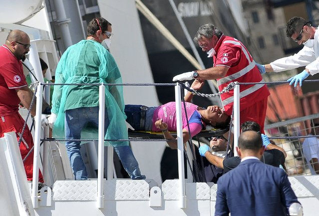 A migrant is helped to disembark from Italian Coast Guard vessel Diciotti in the Sicilian harbour of Palermo, Italy, August 20, 2015. (Photo by Guglielmo Mangiapane/Reuters)
