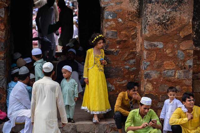 A young Indian muslim girl stands on the staircase ahead of offering prayers during Eid al-Fitr among the ruins of the Feroz Shah Kotla mosque in New Delhi on July 7, 2016. The three-day festival, which begins after the sighting of a new crescent moon, marks the end of the fasting month of Ramadan during which devout Muslims abstain from food and drink from dawn to dusk. (Photo by Chandan Khanna/AFP Photo)