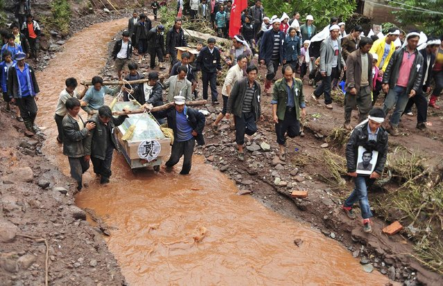 Villagers carry the coffin and portrait of a victim who was killed by a flash flood as they wade through a stream during a funeral in Sujia village of Zhaotong, Yunnan province July 17, 2012. The flood caused by heavy rain falls in Sujia Village of Zhaotong since Sunday, left 2 dead and 8 injured. Torrential rain last week affected more than 2 million people in several southern Chinese provinces, according to local authorities, Xinhua News Agency reported. (Photo by Wong Campion/Reuters Photo)