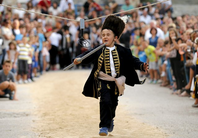 A child runs during the Children's Alka competition in Vuckovici village, Croatia, August 23, 2015. (Photo by Antonio Bronic/Reuters)