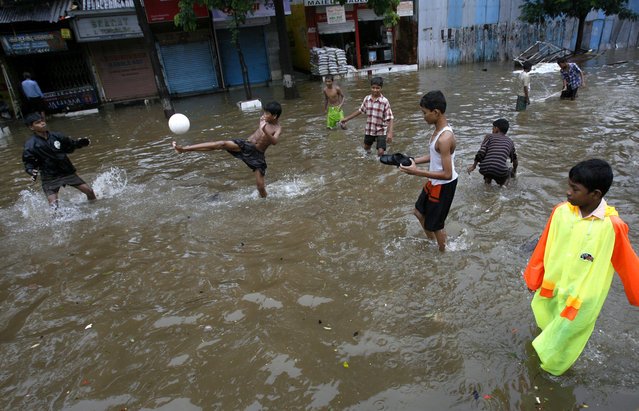 Children play football on a waterlogged street in Mumbai June 24, 2007. (Photo by Arko Datta/Reuters)