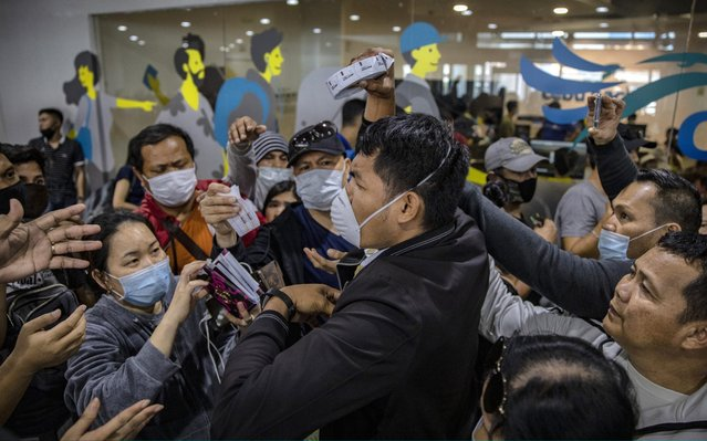 Airport security staff attempt to control the crowd as Filipinos hoping to get on flights out of Manila hours before it is placed on lockdown flock at Ninoy Aquino International Airport on March 14, 2020 in Manila, Philippines. Philippine President Rodrigo Duterte announced on Thursday that he would place some 12 million people in the capital Manila on lockdown and suspend government work for a month to prevent the spread of COVID-19. The Philippines' Department of Health has so far confirmed 98 cases of the deadly coronavirus in the country, with at least 8 recorded fatalities. (Photo by Ezra Acayan/Getty Images)