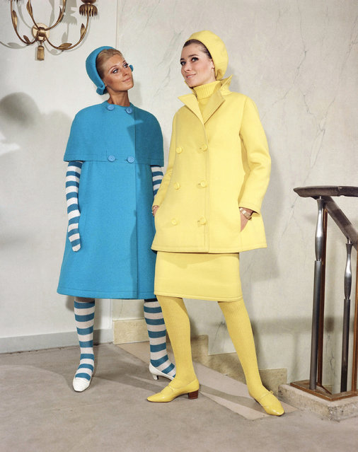 "At left ""Gaspard"" a dark blue woolen coat worn with a matching hat and with blue and white rays woolen gloves and stockings plus white leather shoes. At right ""Thomas"", a yellow woolen ensemble (skirt, long jacket and beret hat) worn over a pullover and matching woolen stockings plus yellow leather shoes. Both dresses were featured at Jacque Heim's fall winter collection, August 27, 1966. (Photo by AP Photo)"