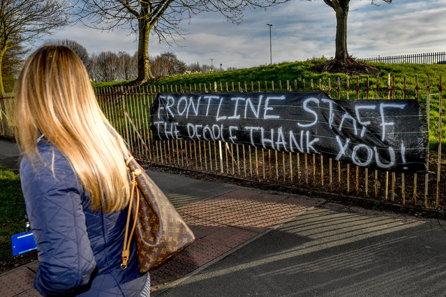 An NHS worker walks past a banner supporting NHS staff outside Salford Royal Hospital on March 22, 2020 in Manchester, UK. Coronavirus (COVID-19) has spread to at least 182 countries, claiming over 13,069 lives and infecting more than 308,592 people. There have now been 5,018 diagnosed cases in the UK and 233 deaths. (Photo by Anthony Devlin/Getty Images)