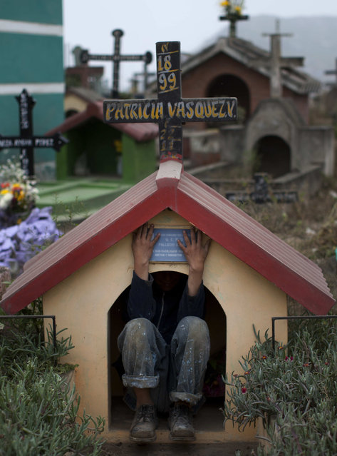 Juan Trujillo Leon, 12, takes a break from selling bottled water and plays in a niche at the Virgen de Lourdes cemetery, where many are gathering to mark the Day of the Dead holiday, in Lima, Peru, Friday, November 2, 2012. (Photo by Rodrigo Abd/AP Photo)