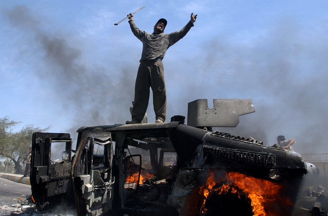 An Iraqi man celebrates atop of a burning U.S. Army Humvee in the northern part of Baghdad, Iraq, Monday, April 26, 2004. An explosion leveled a building in northern Baghdad on Monday, setting four U.S. Humvees nearby on fire. At least one U.S. soldier and several Iraqis were wounded. The cause of the explosion was not immediately known.  This photograph is one in a portfolio of twenty taken by eleven different Associated Press photographers throughout 2004 in Iraq. (Photo by Muhammed Muheisen/AP Photo)