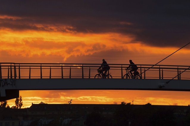 In this September 1, 2017 photo cyclists cross the Molen bridge in the light of the setting sun in Dresden, Germany. (Photo by Sebastian Kahnert/DPA via AP Photo)