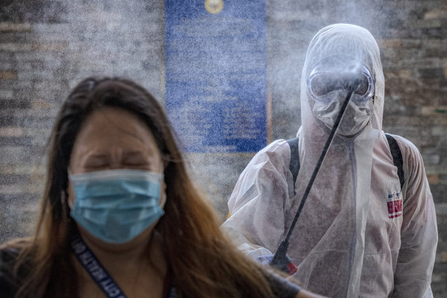 A government employee reacts as she is sprayed with disinfectant before entering a government office building to curb the spread of COVID-19 on March 19, 2020 in Pasig city, Metro Manila, Philippines. The Philippine government has sealed off Luzon, the country's largest and most populous island, to prevent the spread of COVID-19. Land, sea, and air travel has been suspended, while government work, schools, businesses, and public transportation have been ordered shut in a bid to keep some 55 million people at home. The Philippines' Department of Health has so far confirmed 217 cases of the new coronavirus in the country, with at least 17 recorded fatalities. (Photo by Ezra Acayan/Getty Images)