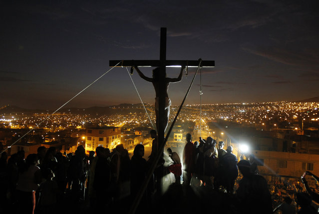 An actor playing the role of Jesus Christ hangs from a cross during the re-enactment of the crucifixion of Jesus Christ during Holy Week at Mi Peru, a shanty town on the outskirts of Lima April 17, 2014. (Photo by Enrique Castro-Mendivil/Reuters)