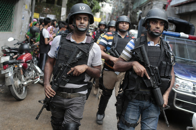 Members of a Bangladeshi special force leave the premises of a five-story building that was raided by police in Dhaka, Bangladesh, Tuesday, July 26, 2016. Police in Bangladesh's capital raided a five-story building Tuesday that was used as a den by suspected Islamic militants, killing nine of them, the country's police chief said. Police said they belonged to a Bangladeshi group blamed for an attack on a Dhaka cafe earlier this month in which 20 hostages, mostly foreigners, were killed and had been planning another large-scale assault. (Photo by AP Photo)
