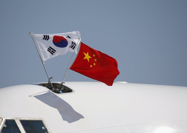 South Korea (L) and China's flags flutter atop a aircraft as South Korean President Park Geun-hye (not in picture) arrives at Beijing Capital International Airport in China, September 2, 2015, ahead of attending the commemoration of the 70th anniversary of the end of World War Two. (Photo by Kim Kyung-Hoon/Reuters)