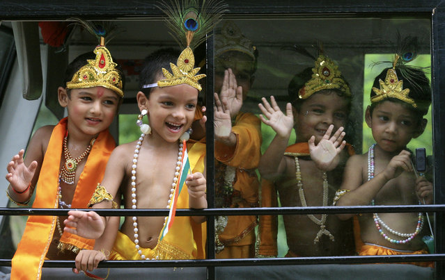 "School children dressed as Krishna wave from inside a bus on the eve of ""Janamashtmi"" celebrations in Chandigarh August 13, 2009. (Photo by Ajay Verma/Reuters)"