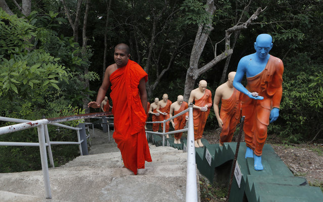A Sri Lankan Buddhist monk climbs the steps past statues at a deserted temple during curfew on Buddha Jayanthi, a day that celebrates the birth of the Buddha, in Colombo, Sri Lanka, Thursday, May 7, 2020. Sri Lanka has again reimposed a 24-hour countrywide curfew until next Monday, as part of stringent measures to contain the spread of the coronavirus. (Photo by Eranga Jayawardena/AP Photo)